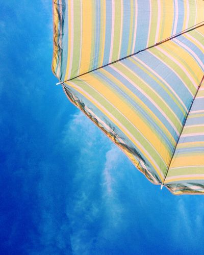 Low angle view of beach umbrella against blue sky