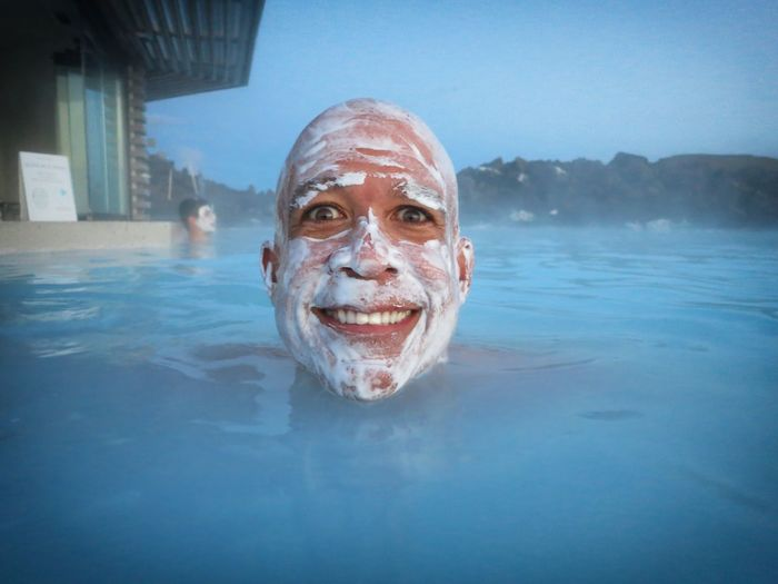 Portrait Of Cheerful Man With Mud Mask In Blue Lagoon