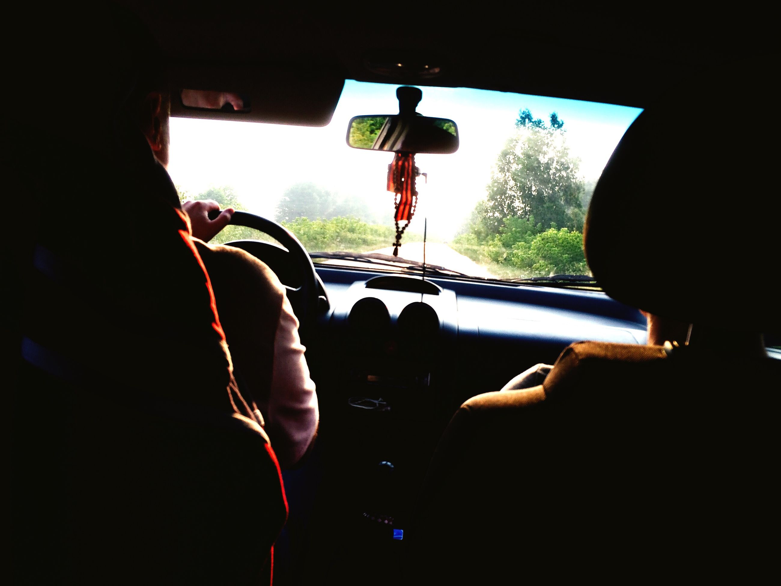 window, car interior, vehicle interior, indoors, silhouette, glass - material, car, transparent, mode of transport, transportation, windshield, land vehicle, men, driving, person, dark, holding, car point of view, day, multi colored, flying