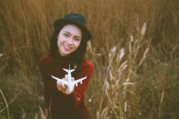 Portrait of smiling young woman holding model airplane while standing by plants