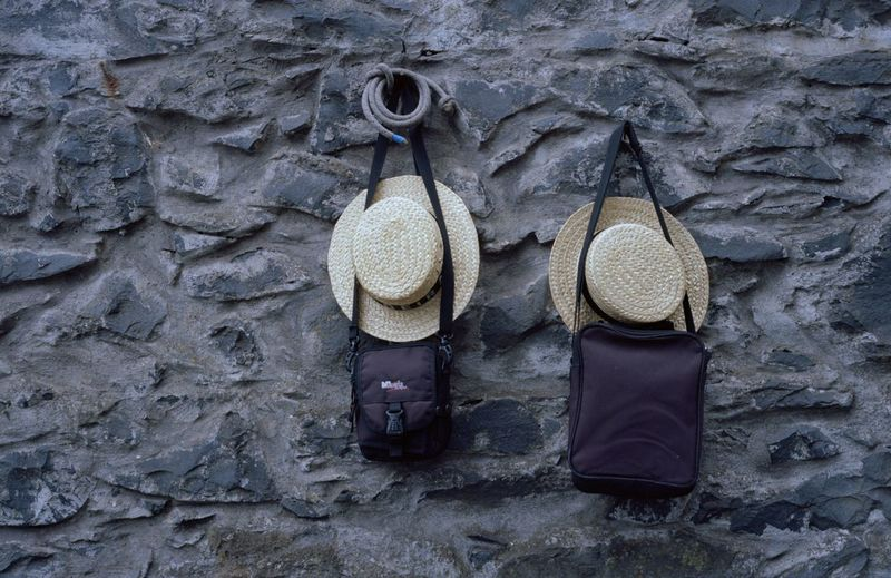 Low Angle View Of Hats Hanging On Stone Wall