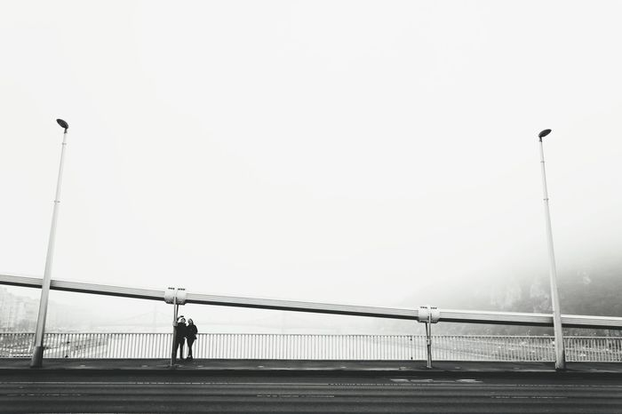 Black And White Friday Connection Bridge - Man Made Structure Fog Suspension Bridge Outdoors Social Issues Built Structure Silhouette Travel Destinations Sea Sky Beach Steel City Electricity Pylon People Day Budapest Bridge