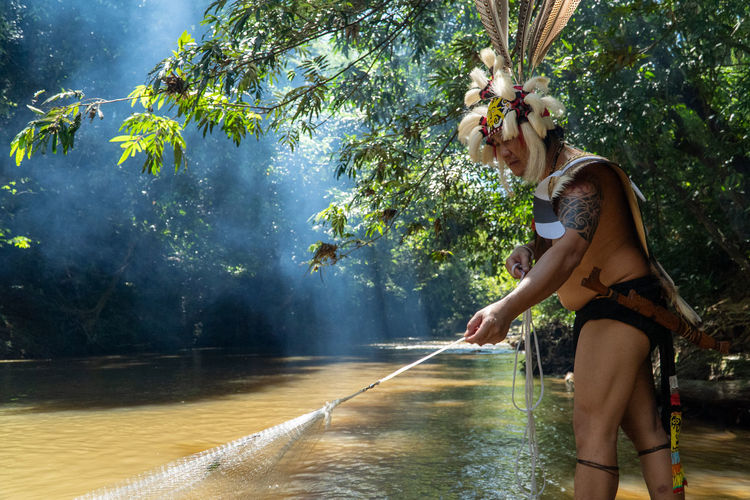 A man wearing traditional borneo clothes is waving a fishing net