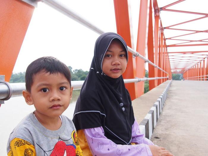 Portrait Of Cute Siblings Sitting On Bridge Over River