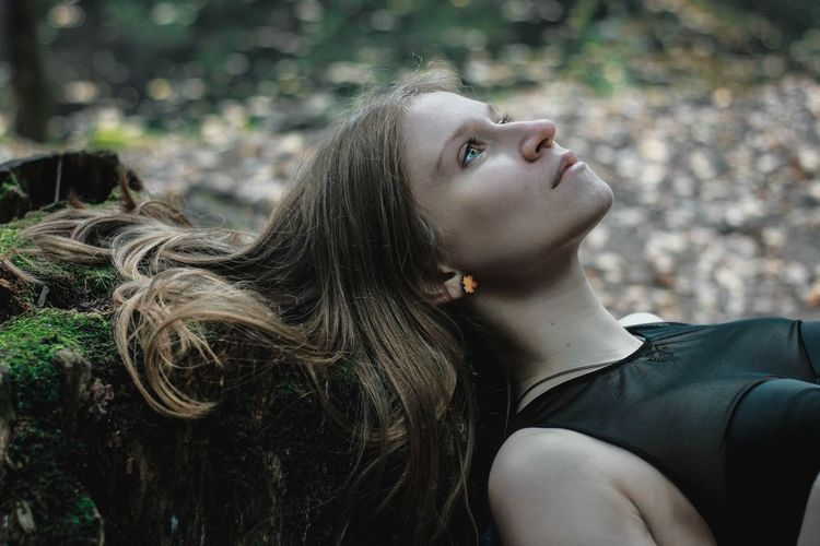 Close-up of young woman against tree