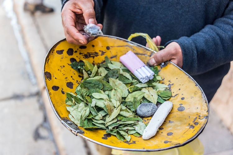 Coca leaves and cigarettes for sale in Potosi, Bolivia Andean Andes Bolivia Cigarette  Coca Color Colorful Colour Culture Food Freshness Green Color Holding Leaf Leaves Person Plant Potosi Potosi Bolivia South America Tourism Tradition Traditional Travel Yellow