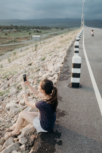 High angle view of woman photographing with smart phone while sitting on road