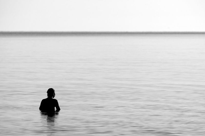 Rear view of silhouetted person in the sea