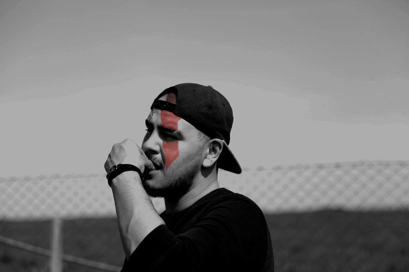 Thoughtful man with red face paint wearing cap against clear sky
