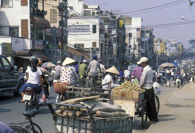 People On Road Against Buildings In City