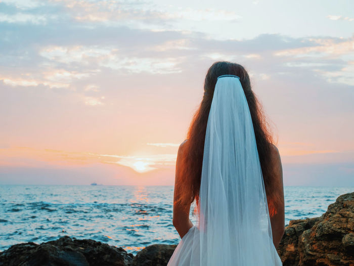 Unrecognizable girl in wedding luxury dress watching sunrise on sea shore. Bride on a rocks. Woman enjoying happy moments with nature. Adult Beauty In Nature Cloud - Sky Hair Hairstyle Horizon Horizon Over Water Lifestyles Looking At View Nature One Person Outdoors Real People Rear View Scenics - Nature Sea Sky Standing Sunset Water Women