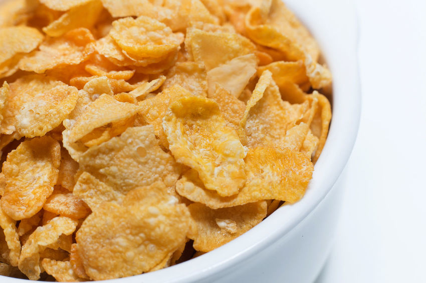 The image Close up Cornflakes cereal breakfast in white bowl on white background. CornflakesCrew Bowl Close-up Cornflakes Cornflakes & Coffee Flavors Cornflakes And Milk Crunchy Day Food Food And Drink Freshness Heap Indoors  No People Ready-to-eat Snack Studio Shot