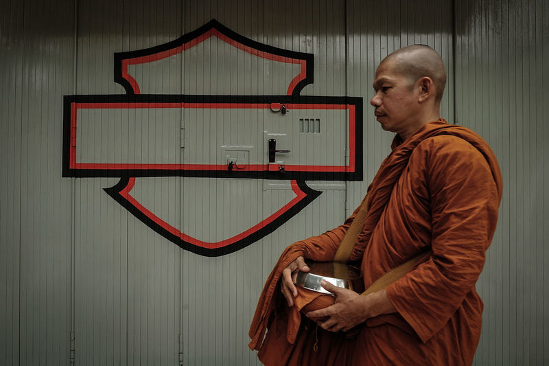 Side view of monk standing against wall