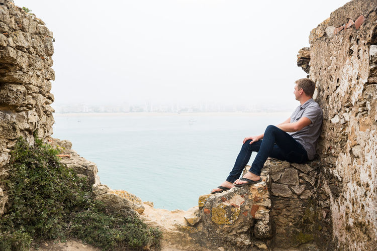 Side view of young man sitting on rock formation by sea against sky