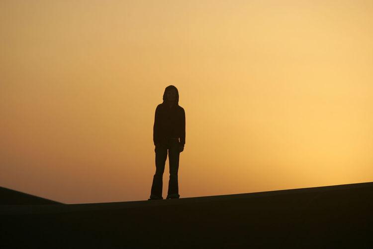 Man standing at desert against sky during sunset
