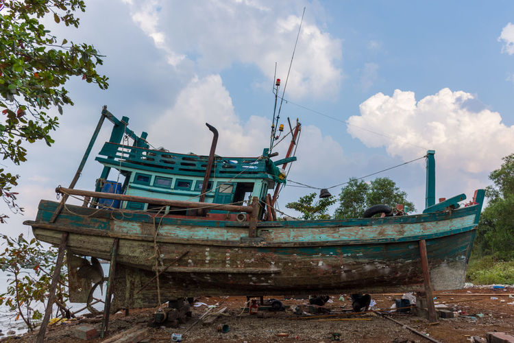 An old traditional fishing boat out of the sea in mesh dry dock yard waiting for repairs with blue sky and cloud back ground. Abandoned Blue Sky Boat Yard Clouds Day Dry Dock Fishing Boat Harbour In Need Nautical Vessel No People Old Old Paint Outdoors Repairs Rotten Ship Sky Traditional Tree Vessel Wooden