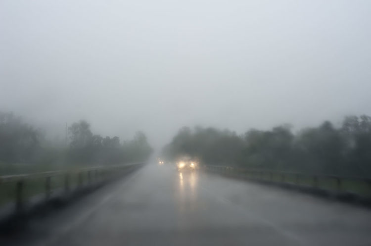 driving on a stromy day headlights from oncomign traffic shrouded in rain and mist Blur Blurred Motion Car Cars Color Dangerous Grey Hazardous Headlights Lights Rain Raining Rainy Stormy Traffic Vehicle Wet