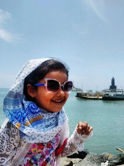 Girl with sunglasses on beach against sky