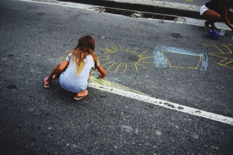 High angle view of girls chalk drawing on road