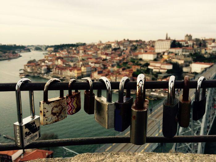 Close-Up Of Love Locks On Bridge Over River Against Sky