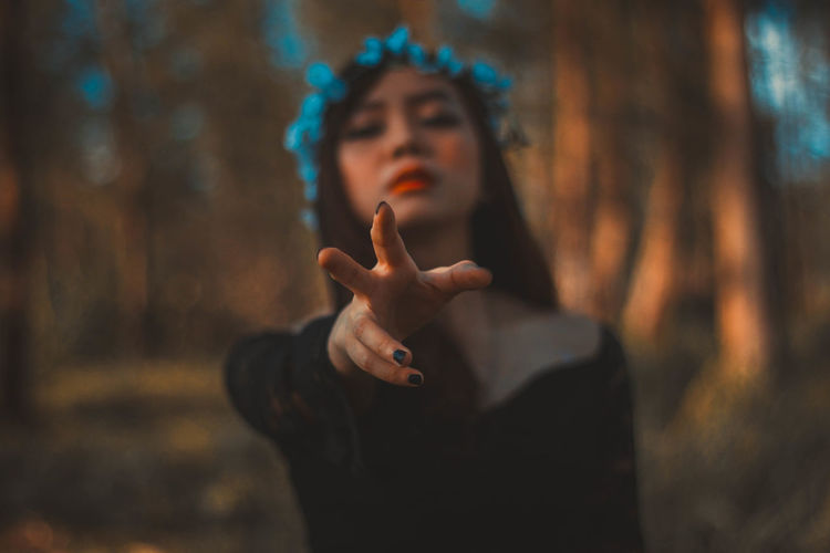 Portrait of beautiful woman gesturing in forest