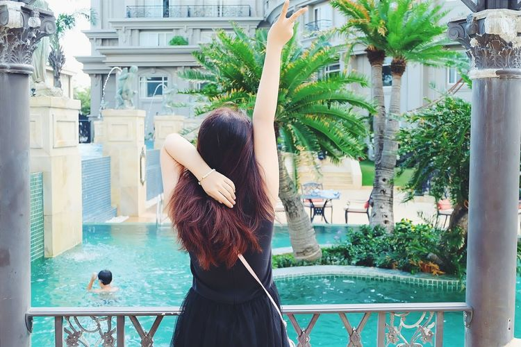 Rear View Of Woman Showing Peace Sign While Standing By Railing At Tourist Resort