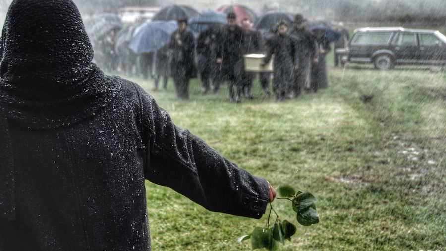 Rear view of man holding leaves with people carrying coffin at cemetery during snowfall