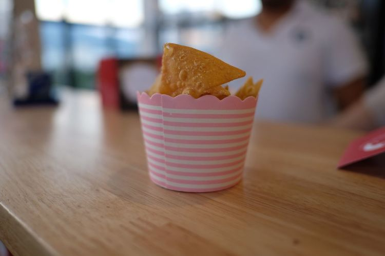 Close-up of nacho chips in bowl on wooden table