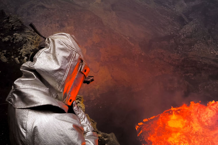 Man Wearing Fire Protection Suit While Standing Against Lava