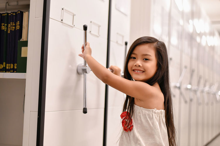 Portrait of smiling girl opening locker