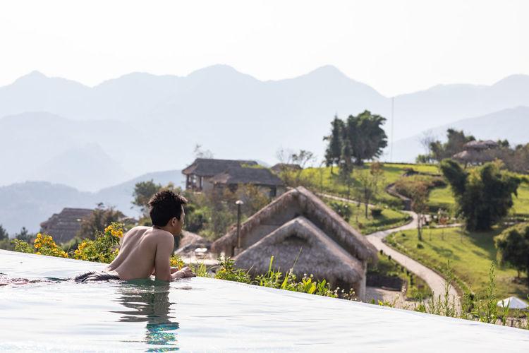 Man relaxing by field in infinity pool