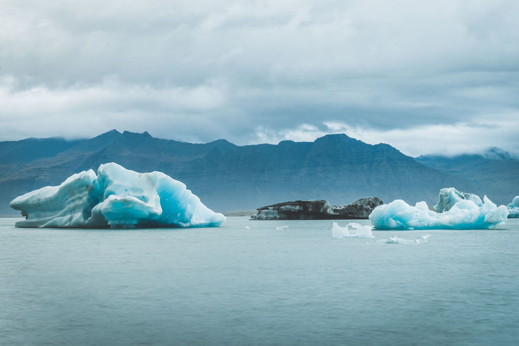 Scenic view of glaciers in sea against mountains