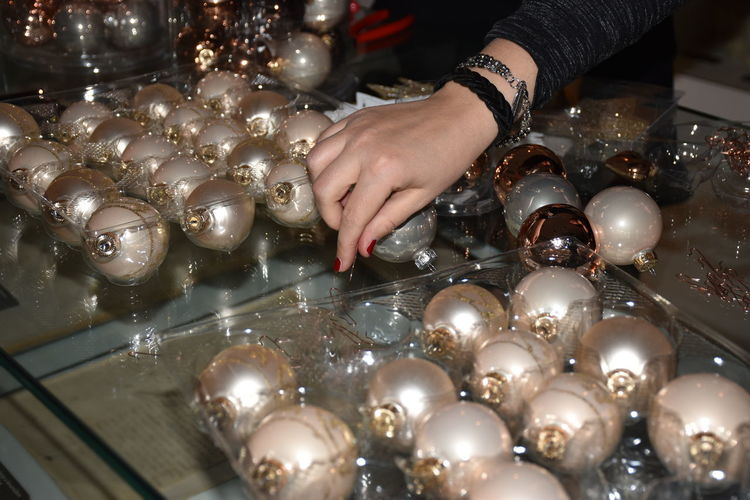 Cropped Image Of Woman Arranging Christmas Baubles