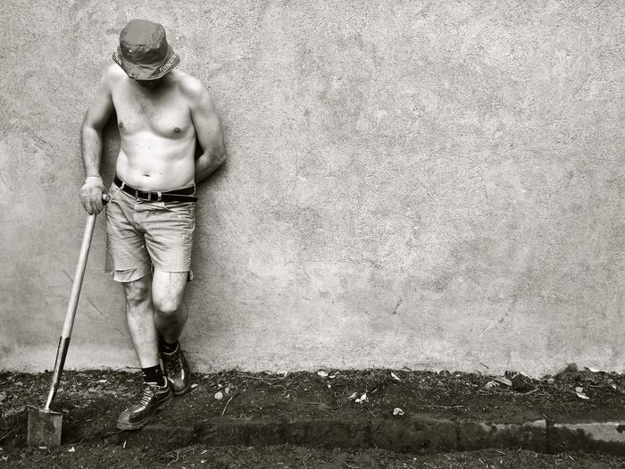 Full length of shirtless man standing with shovel against wall