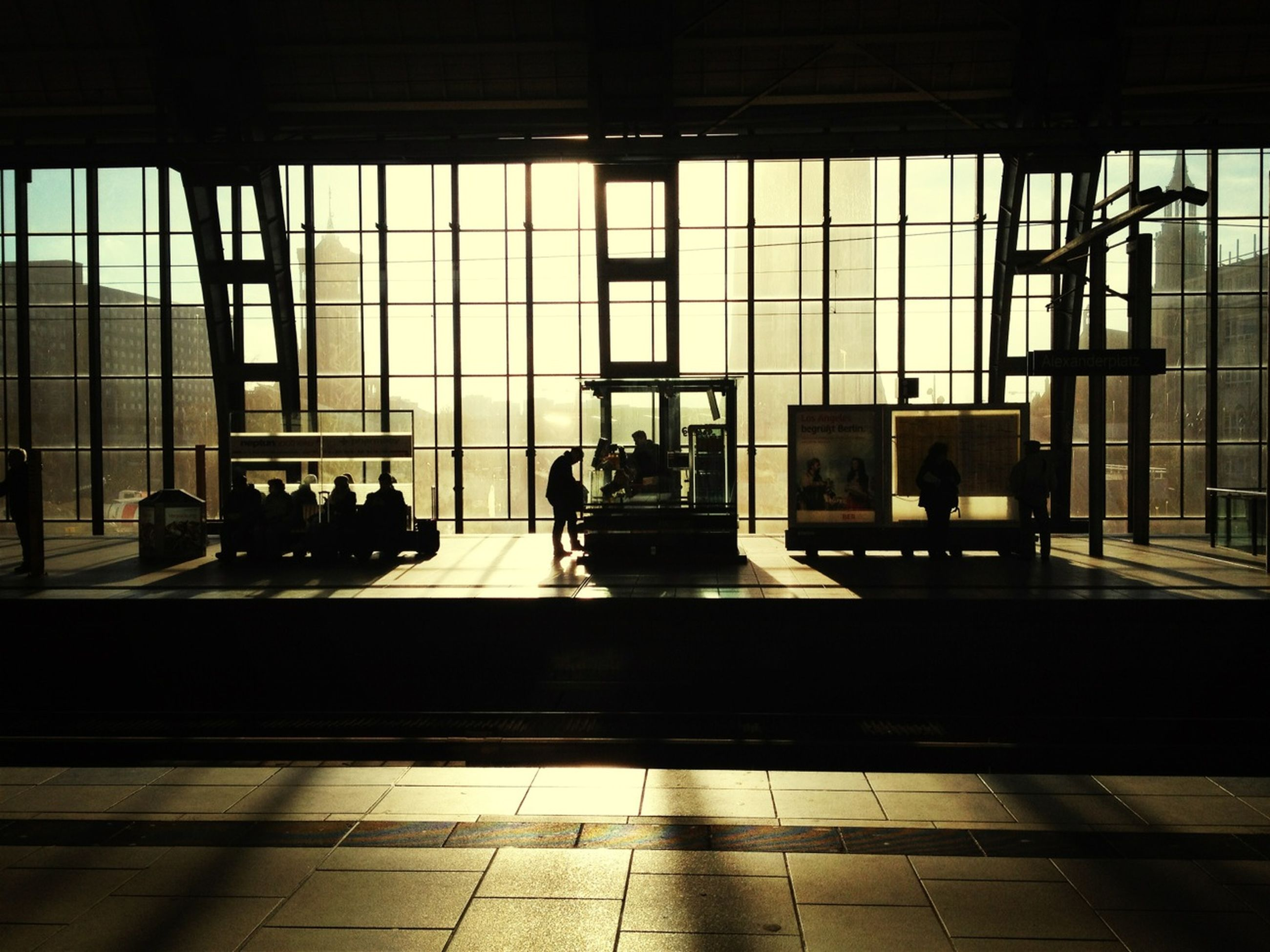 indoors, architecture, built structure, window, glass - material, transparent, men, silhouette, modern, building exterior, city, sunlight, person, glass, lifestyles, reflection, day, medium group of people, city life
