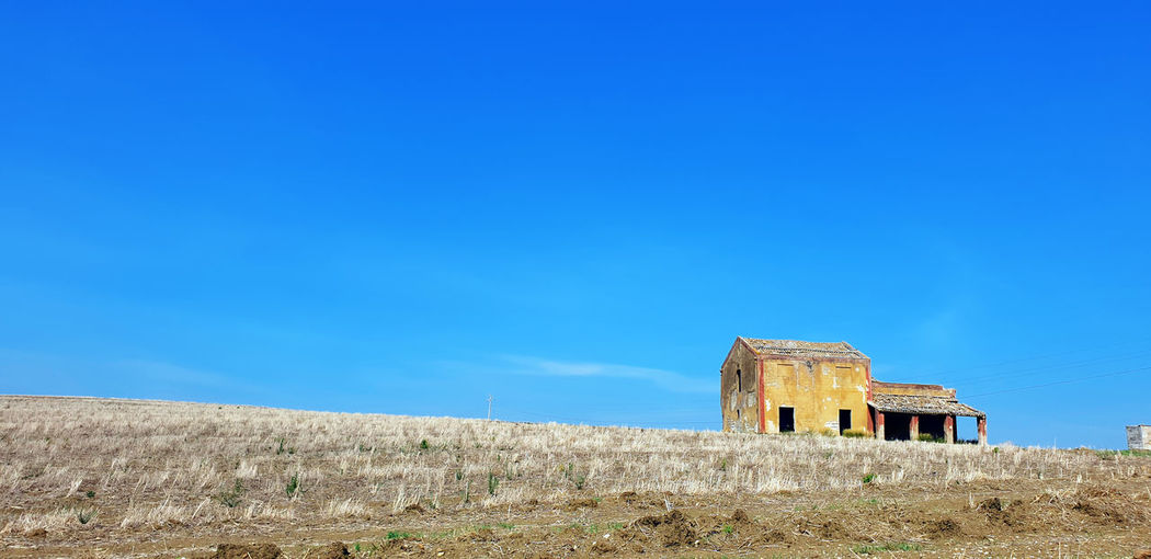 Old ruin on field against clear blue sky