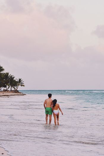 Rear View Of Couple Walking In Sea Against Cloudy Sky During Sunset