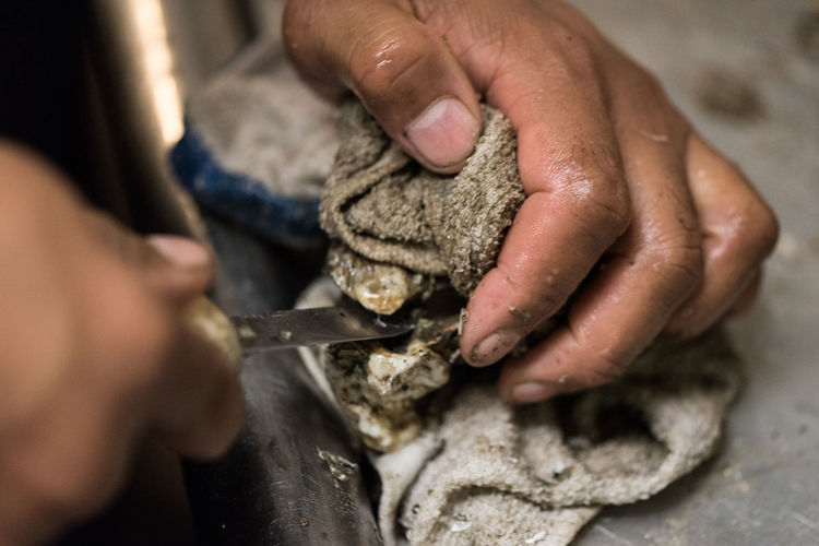 Cropped image of person shucking oyster on table