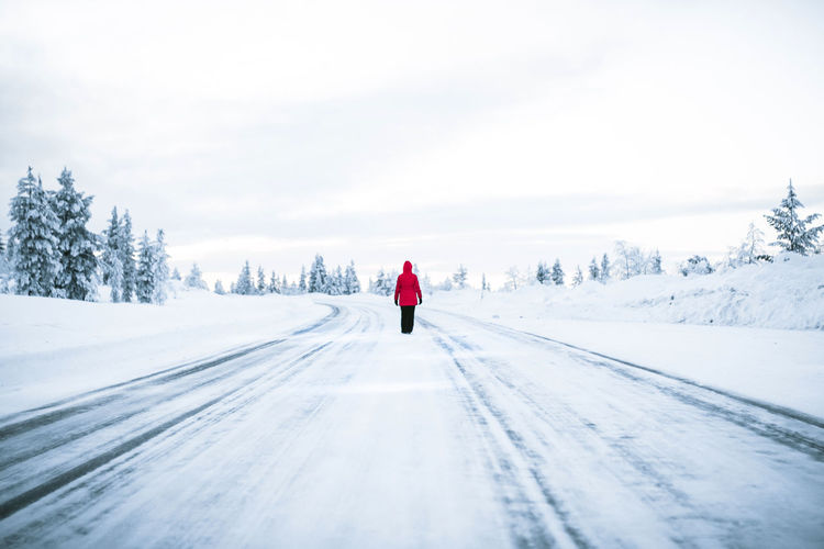 Rear view of person walking on snow covered street against sky
