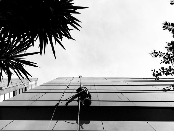 Low Angle View Of Man Working On Rope Against Sky
