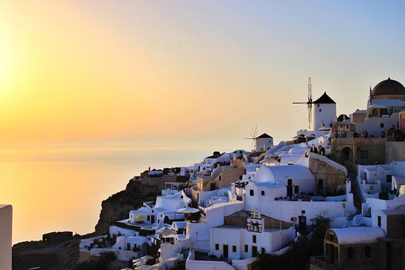 Traditional windmills amidst houses at santorini against sky during sunset