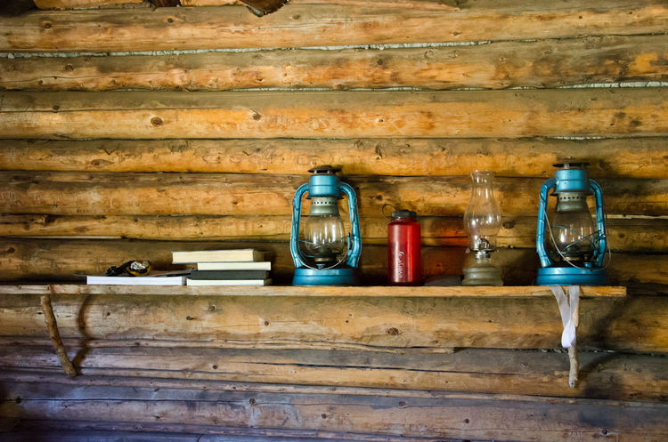 Old and new on shelf in log cabin Backpacking Dark Hiking Rustic Aged Bottle Close-up Day Food And Drink Indoors  Interior Lamp Lamps No People Old-fashioned Vintage Water Bottle  Wood - Material