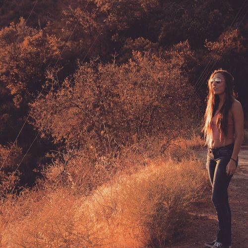 Young woman in sunglasses standing on road at forest during sunset