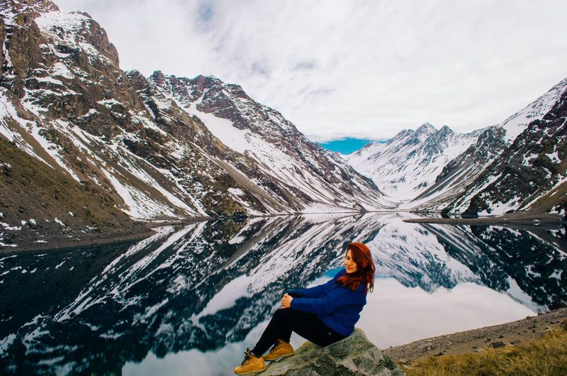 Full length of woman sitting by lake against snowcapped mountain