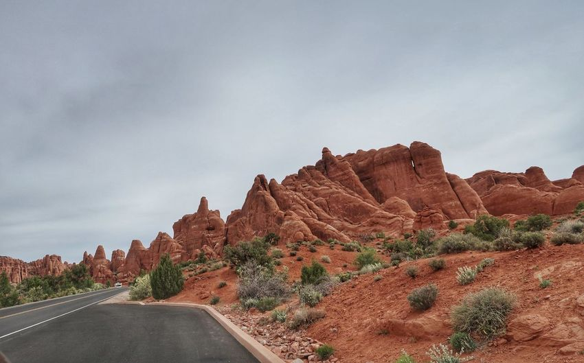 Road by rock formations against sky