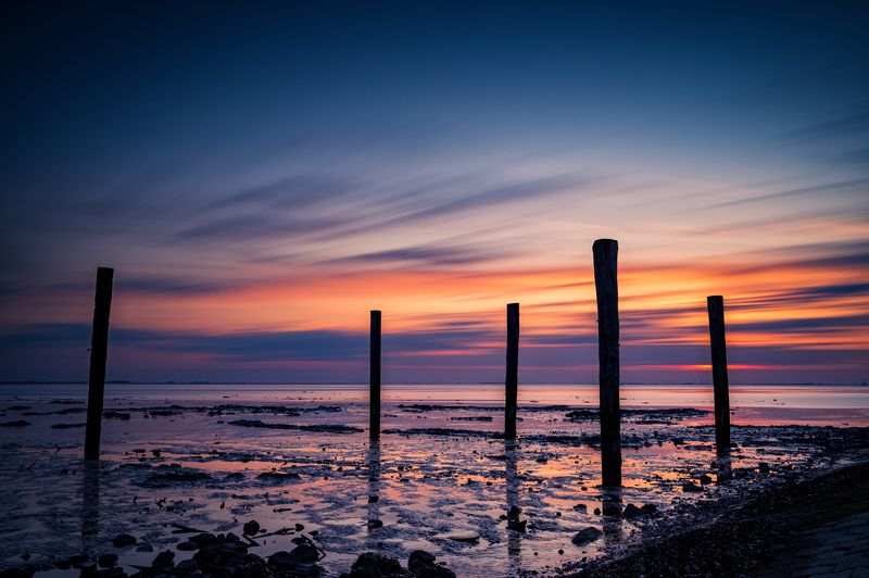 Silhouette wooden posts on beach against sky during sunset