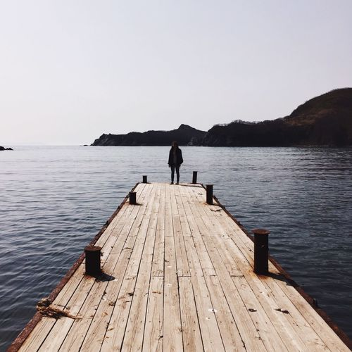 WOMAN STANDING ON WOODEN JETTY ON TRANQUIL SEA
