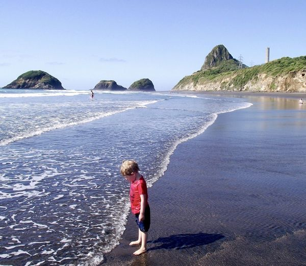 Side view of boy standing on shore at beach against sky