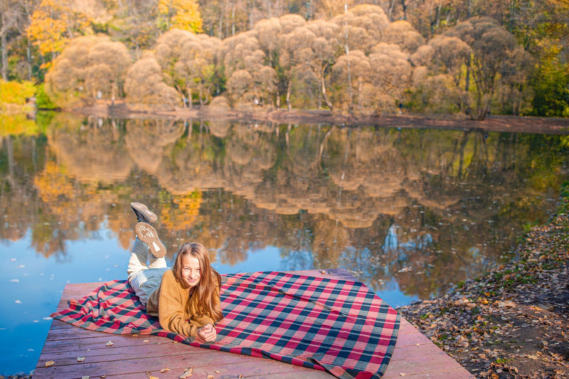 Reflection of young woman sitting on lake during autumn