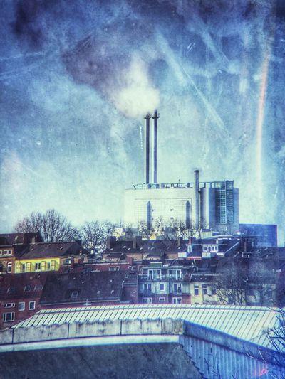 Smoke stacks in factory against sky